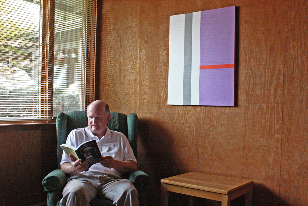 Director of Christ Peace House of Prayer Vince Eimer poses in front of a piece of artwork he painted. According to Eimer, he often uses contemplative prayer while painting.