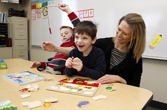 Sam Chambers, left, plays a fishing game while Keegan Burns and CARE and Worship teacher Kristin Brokaw complete a puzzle as they get ready for their Sunday morning class to start at St. Michael the Archangel Parish in Leawood.