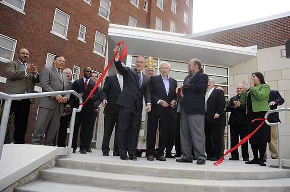 From left, Donnelly trustee Bill Dunn Jr. (with ribbon) is joined by Henry W. Bloch and trustee and alum George Breidenthal in cutting the ceremonial ribbon on Donnelly College's new community event center on April 5, as Archbishop Joseph F. Naumann, Donnelly trustees and community leaders look on. The three men co-chaired Donnelly's Transformations campaign. Photo by Elaina Cochran.