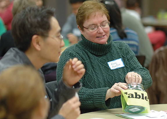 Good Shepherd. Shawnee, parishioner Mary Mueller (right) reads an icebreaker question she's drawn at the immigration round table as Hoseop Cha, a member of the Korean Catholic Church at Holy Trinity in Lenexa, waits his turn. Photo by Jill Ragar Esfeld.