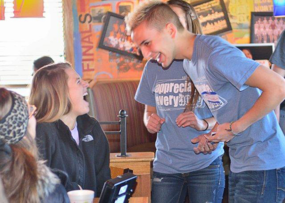 It wasn't all work at the REbeL pancake breakfast fundraiser. Sharing a laugh are seniors Abby Schmitz (left), Olathe East, and Shane Smith, Blue Valley Northwest in Overland Park. Both students are members of REbeL chapters at their high schools. Photo by Jill Ragar Esfeld.