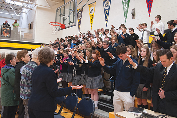 Students at Maur Hill-Mount Academy in Atchison bless the Benedictine Sisters of Atchison during an assembly on March 21 at the school. The Sisters are celebrating their 150th anniversary in the Archdiocese of Kansas City in Kansas with a year's worth of celebrations.