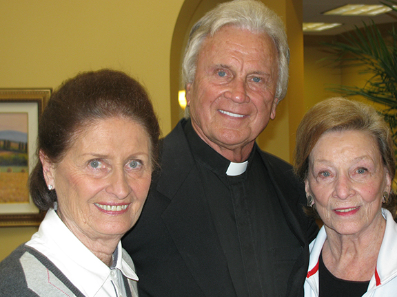 LEAVEN PHOTO BY SHEILA MYERS Father Robert Pflumm poses at Santa Marta with his sisters, Janet Lillis, left, and Jane Kelly, right. After serving the archdiocese for more than 50 years, Father Pflumm has retired to Santa Marta, just a few miles from where he grew up.