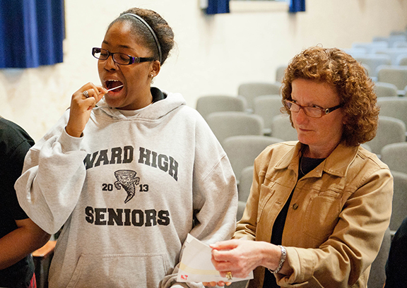 "Elexis Whitmore, left, a senior at Bishop Ward High School in Kansas City, Kan., swabs the inside of her mouth as part of the national bone marrow donor registry process. Mary Spangler, right, with Ward's development office, assists during this inaugural ""18 and Swabbin'"" drive, which was held at the high school on April 10."