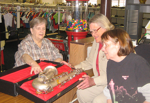 Cookie Kovar, center, manager of Sacred Heart Variety and More, and two of her volunteers — Allyson Trautloff, left, and Noreen Wilderson, right — look over a recently donated antique saxophone.