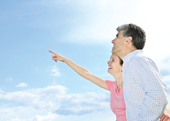 Mature romantic couple of baby boomers looking at the sky
