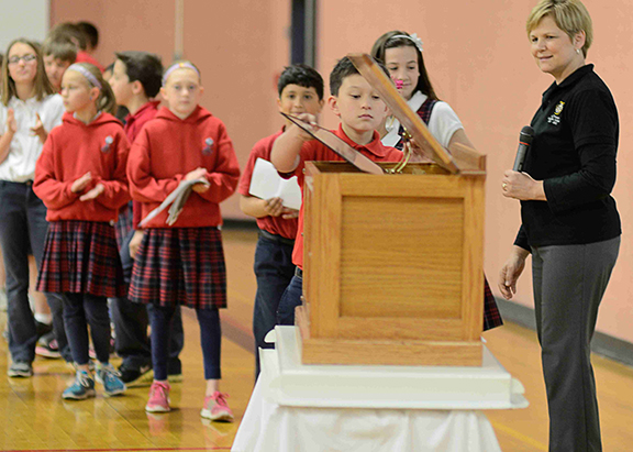 Holy Trinity principal Martha Concannon looks on as third-grader William Ashley adds a collage to the time capsule as memorabilia from Phyllis McEntire's class.