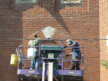 Construction workers renovate the exterior of Sts. Peter and Paul Church in Seneca in June. The church is undergoing a major renovation. Work is expected to be completed sometime next year.