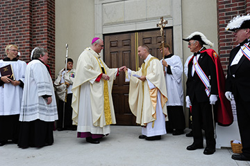 "Leaven photo by Elaina Cochran Archbishop Joseph F. Naumann hands the key to the new St. Stanislaus Church to pastor Father Bruce Ansems. Hundreds of parishioners and visitors gathered outside the church in Rossville before the 4 p.m. dedication Mass on Aug. 4. Father Ansems unlocked the door and the crowd processed inside for the Mass. While the building is beautiful, the archbishop said in his homily, ""What's most beautiful is to see it filled with the people of God."""