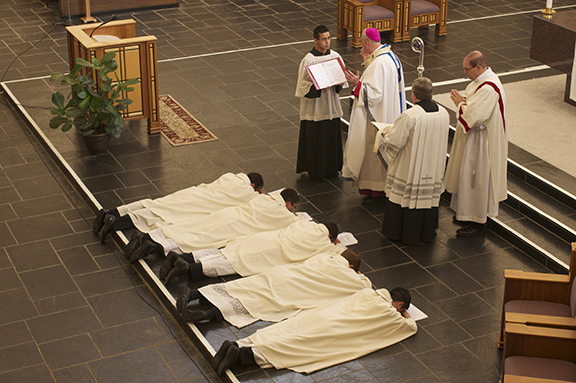 The five priests who make up the male branch of the Apostles of the Interior Life lie prostrate before the altar at Savior Pastoral Center on Aug. 22 as the group is made a clerical public association of the faithful. Archbishop Joseph F. Naumann signed the decree that make the Apostles' new status official. A female branch of the Apostles of the Interior Life has already formed in the archdiocese. Leaven photo by Don Wolf
