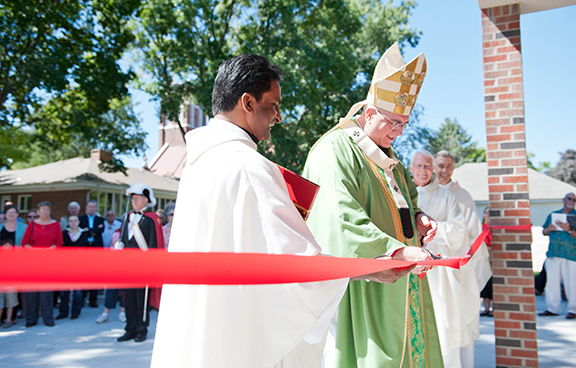 Father Marreddy Yeruva, pastor of St. Theresa Parish in Perry, assists Archbishop Joseph F. Naumann in a ribbon-cutting ceremony to officially open St. Theresa's new hall on Sept. 9.