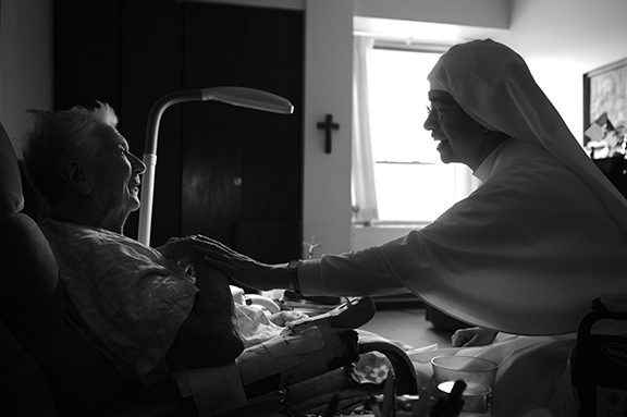Sister Lucero Garcia visits with one of her patients, Barbara Carroll, during her rounds. Sister Lucero is more than a nurse — she brings Communion to her patients, prays with and for them, and is always willing to listen.