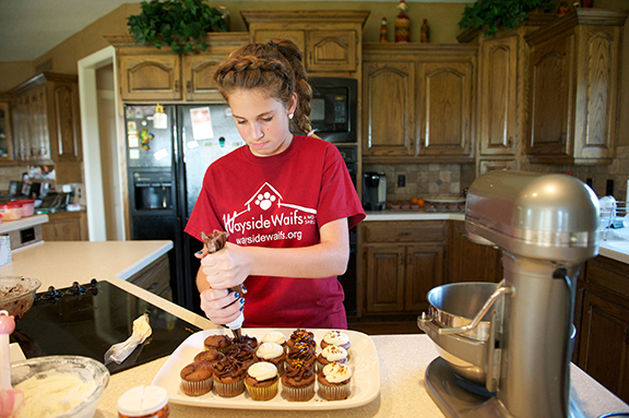 Annie Toussaint, a seventh-grader at Holy Trinity School in Lenexa, frosts a batch of chocolate cupcakes. Annie, 13, raised so much money for Wayside Waifs by selling her homemade cupcakes in 2011, she was named grand marshal of the organization's 2012 Strutt With Your Mutt event Sept. 22.