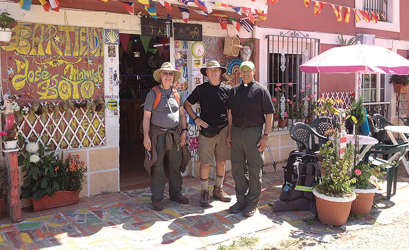 PHOTO COURTESY OF TONY STUBBS From left, Father Mike Stubbs, Tony Stubbs and Father Peter Jaramillo, SSA, stand outside a storefront in Pola de Allande, Spain, after a day of walking the Way of St. James via the Camino Primitivo.