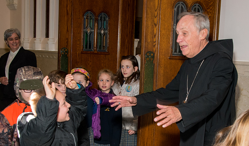 Abbot Primate Notker Wolf greets Jaxson Vice, a first-grader at St. Benedict School in Atchison, following Mass at Mount St. Scholastica. Trailing behind Jaxson are fellow first-graders Dayton Olson, Connor Moore, Abby Baniewicz, Hailey Gibson, and Kaitlyn Folsom. Sister Judith Sutera, OSB, can be seen at left in the background.