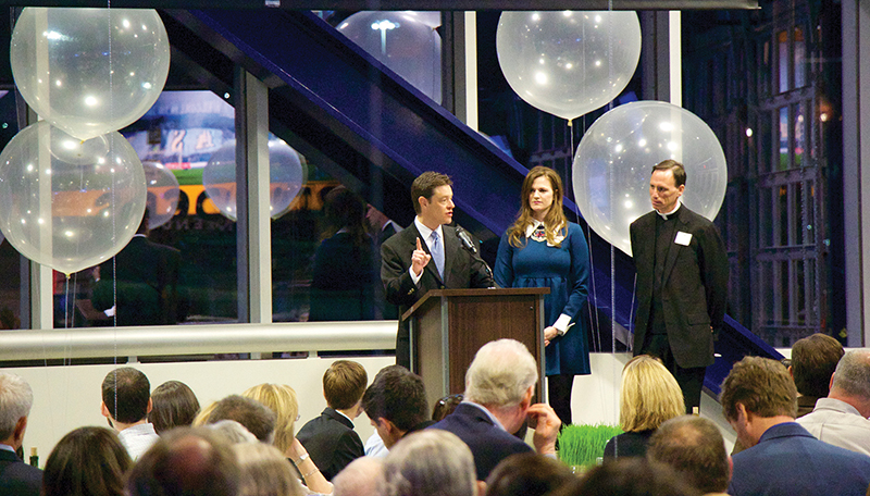 Toby Cook, left, Kansas City Royals vice president of community affairs and publicity (and master of ceremony for the evening), Laurel Sharpe, executive director of advancement for the St. Lawrence Catholic Campus Center, and Father Steve Beseau, chaplain/director of the St. Lawrence Center, kick off a new era for the center on Feb. 7. Attendees enjoyed dinner and a tour of the stadium that is home to Sporting Kansas City in Kansas City, Kansas.