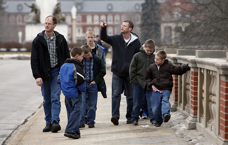 Part of the group of nine dads and 20 boys take a stroll around the campus  at St. Mary of the Lake Seminary in Mundelein. They were in town for a father/son trip to discover seminary life and watch the Father Pat O'Malley Invitational on Jan. 31.  (Karen Callaway/Catholic New World)