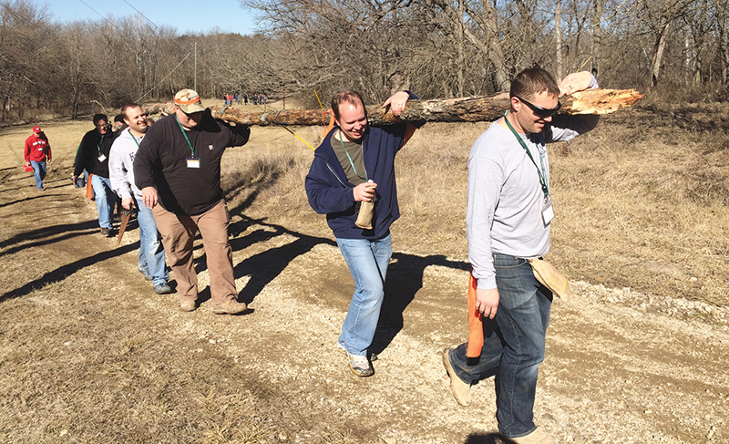 Steve Johnson, Jamie Sheerin — all members of Prince of Peace Parish in Olathe — and Doug Kuhn, a member of the Basilica of St. Fidelis in Victoria, carry the wood that will be used to build the altar as a life-sized illustration of the burnt offering of Abraham and Isaac.