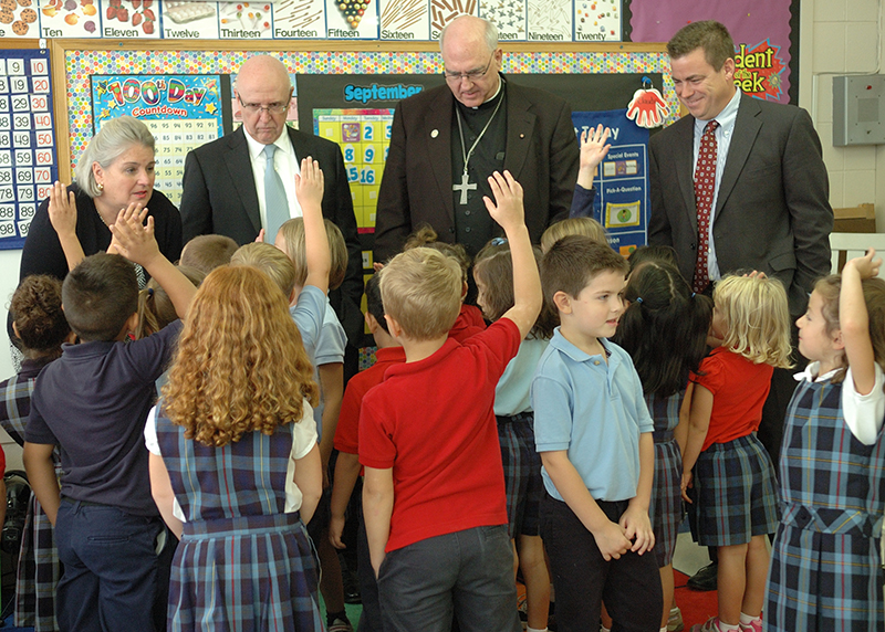 Catholic Education Foundation Angels Among us honorees Bridget and John Murphy talk to first-graders during a visit to St.Paul Grade School in Olathe as Archbishop Joseph Naumann and CEF board chair Hamp Henning look on.