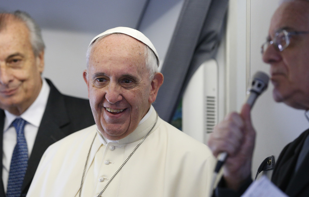 Pope Francis greets media aboard his flight out of Rome July 5. (CNS photo/Paul Haring)