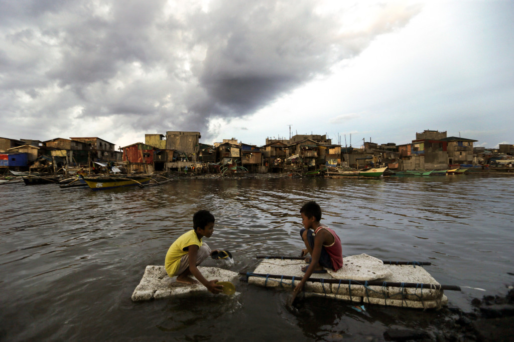 "Children paddle in water in Navotas City, Philippines, May 10. The Federation of Asian Bishops' Conferences wants to set up 22 climate change desks that would support action plans to mitigate the impact of climate change and to study Pope Francis' ""Laudato Si'"" encyclical. (CNS photo/Ritchie B. Tongo, EPA)"