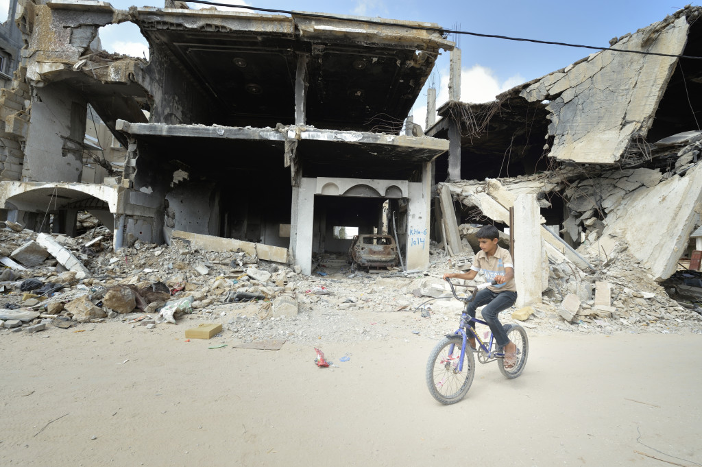A boy rides his bike amid the ruins of Khan Younis, Gaza Strip, June 9. Houses in the area were destroyed during the 2014 war between Israel and the Hamas government of Gaza. (CNS photo/Paul Jeffrey) See GAZA-HOUSING July 17, 2015.