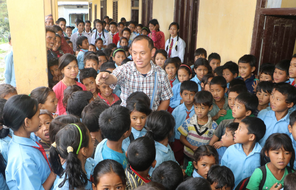 Salesian Father Savio Rai entertains students at the government-run school in at Chaughare, Nepal, July 9. A magnitude 7.8 earthquake April 25 destroyed more than 25,000 classrooms in nearly 8,000 schools. (CNS photo/Anto Akkara) See NEPAL-SCHOOLS July 21, 2015.