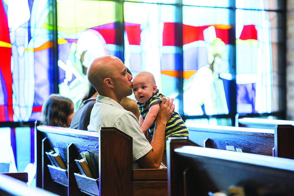 "Gabe Braddy — accompanied by his wife Veronica and children Belle, Joel and Isaiah — holds his baby James during the ""Humanae Vitae"" Mass at Holy Spirit Church in Overland Park last year. This year's Mass will be at Curé of Ars Parish, Leawood. By Doug Hesse"