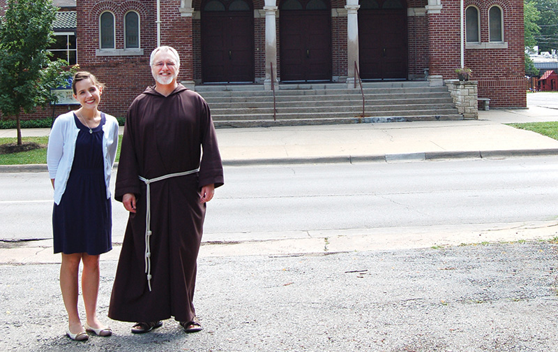 Samantha Romero, director of stewardship and development for St. John the Evangelist Parish in Lawrence, and Father Jeffrey Ernst, OFM Cap., pastor, stand outside the church. St. John was named best place to worship in Lawrence. By Carolyn Kaberline