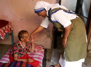 An elderly woman kisses the hand of Sister Marica of the Missionaries of Charity at a home for the elderly in the Pashupatinath temple in Kathmandu, Nepal, July 4. The nuns have been caring for the dying and the elderly sick at the destitute center since 1978, when Mother Teresa initiated the service at the Nepal's holiest Hindu temple. (CNS photo/Anto Akkara)