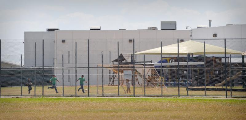 Children play in a double-fenced playground area in 2009 outside the T. Don Hutto Family Residential Facility in Taylor, Texas. The Catholic Legal Immigration Network and the Sisters of Mercy of the Americas decried the Obama administration's effort to have a judge set aside her orders for the release of families being held in immigration detention centers. (CNS photo/Bahram Mark Sobhani).