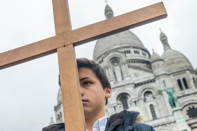 A boy stands with cross outside Sacre Coeur basilica in Paris April 3. Catholic churches in France have been placed under police protection and urged to take extra security measures against possible Islamist attacks before the Aug. 15 feast of the Assumption. (CNS photo/Etienne Laurent, EPA)