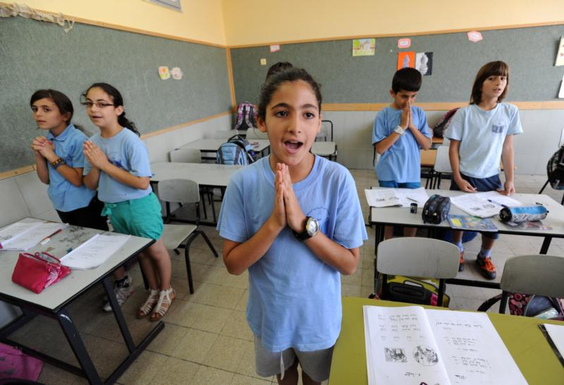 Israeli-Arab fourth-grade students pray in Aramaic during language class in 2012 at Jish Elementary School in Israel. Dozens of Christian schools in Israel may be shutting their doors this coming school year due to increasing restrictions by the Israeli government, Christian educators warn. (CNS photo/Debbie Hill)