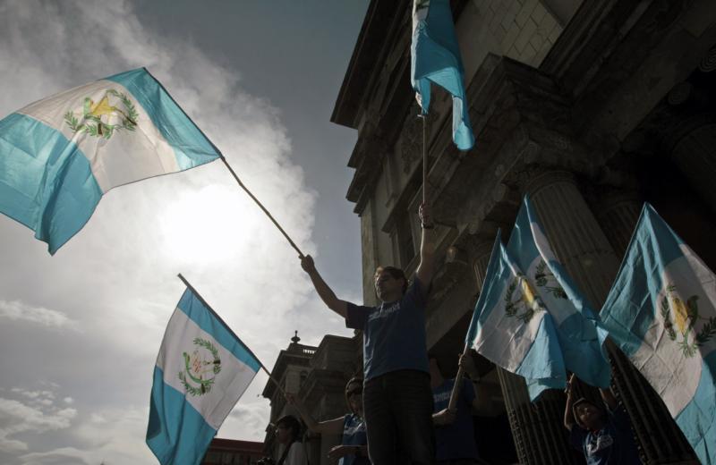 Manifestantes guatemaltecos hacen ondear banderas del país, frente al Palacio Nacional de Cultura de Guatemala, al tiempo que exigen que el presidente guatemalteco actual, Otto Pérez Molina, renuncie a su puesto, el 22 de agosto. (Foto CNS/Esteban Biba, EPA)