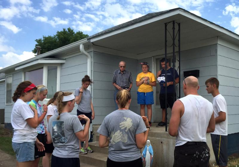 Volunteers with the Prayer and Action summer mission program of the Diocese of Salina, Kan., prays with Father Jarett Konrade and a homeowner in Stockton, Kan., June 4. CNS photo/courtesy Father Gale Hammerschmidt