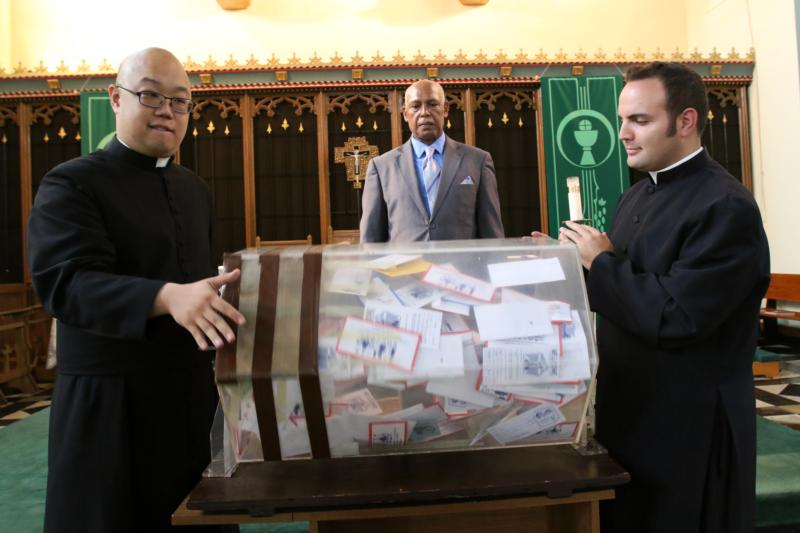 Seminarians Andrew Tsui, left, and Anthony Giacona spin a drum barrel filled with collection envelopes as sacristan Julio Batista looks on following Mass at St. John-Visitation Church in the Bronx borough of New York Sept. 13. A special drawing was used to select parishioners who will receive tickets to Pope Francis' Mass at Madison Square Garden in New York City Sept. 25. (CNS photo/Gregory A. Shemitz)