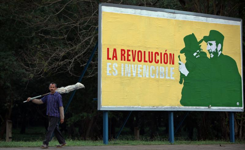 In this Dec. 26, 2014, file photo, a man walks past a Cuban revolutionary banner in Havana. (CNS photo/Alejandro Ernesto, EPA)