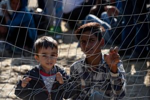 "Migrant children look through a fence as they wait permission to cross the border between Greece and Macedonia Sept. 15. ""Do not abandon victims"" of conflicts in Syria and Iraq, Pope Francis said. (CNS photo/Georgi Licovski, EPA)"