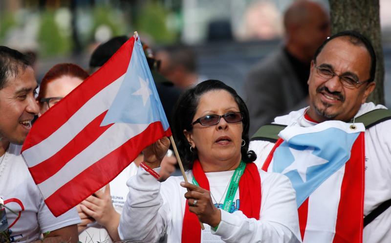A woman holds the flag of Puerto Rico as Pope Francis addresses a crowd at Independence Hall in Philadelphia Sept. 26. In his talk the pope spoke about religious freedom and immigration. (CNS photo/Paul Haring)