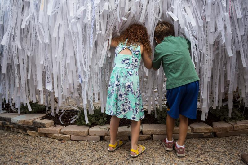 Leah Pepsin, 6, and Lucas Daniel, 6, both from Philadelphia, look through prayer ribbons at the Knotted Grotto outside the Cathedral Basilica of SS. Peter and Paul during the World Meeting of Families Sept. 25 in Philadelphia. Thousands of visitors added their prayer intentions to the project that was inspired by the image of Mary Undoer of Knots. (CNS photo/Joshua Roberts)