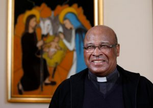 Cardinal Wilfrid Napier of Durban, South Africa, is pictured near an image of the Holy Family after an interview with Catholic News Service in Rome Oct. 7. Cardinal Napier, who is participating in the Synod of Bishops on the family, said several changes in the synod are helping to alleviate any suspicion of the synod being manipulated. (CNS photo/Paul Haring)