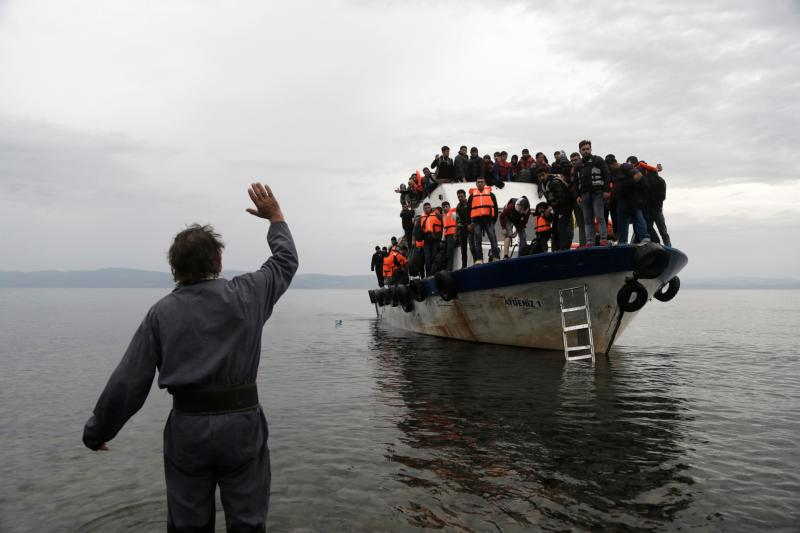 A resident waves to an overcrowded fishing boat carrying migrants after they arrived on the Greek island of Lesbos Oct. 11 after crossing the Aegean sea from Turkey. Greece is bracing for thousands more Syrian and other migrants to land on Lesbos and other key island crossings from Turkey, as those fleeing conflict remain undeterred by the worsening weather and colder autumn temperatures. (CNS photo/Yannis Kolesidis, EPA)