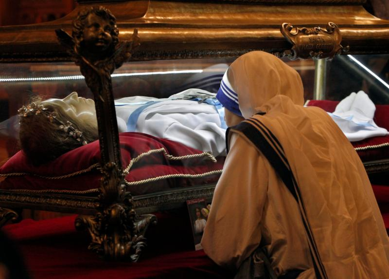 """A member of the Missionaries of Charity venerates the relics of St. Maria Goretti at St. John Cantius Church in Chicago Oct. 12. The major relics, which are virtually all of the skeletal remains of the saint, known as the """"patroness of purity,"""" are on a U.S. """"pilgrimage of mercy"""" this fall that will go to nearly 20 states. (CNS photo/Karen Callaway, Catholic New World)"""