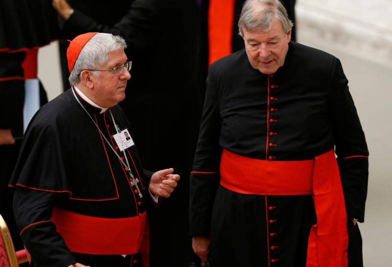 """Cardinal Thomas Collins of Toronto and Australian Cardinal George Pell, prefect of the Vatican Secretariat for the Economy, talk after an event marking the 50th anniversary of the Synod of Bishops in Paul VI hall at the Vatican Oct. 17. At the event Pope Francis outlined his vision for how the entire church must be """"synodal"""" with everyone listening to each other, learning from each other and taking responsibility for proclaiming the Gospel. (CNS photo/Paul Haring)"""