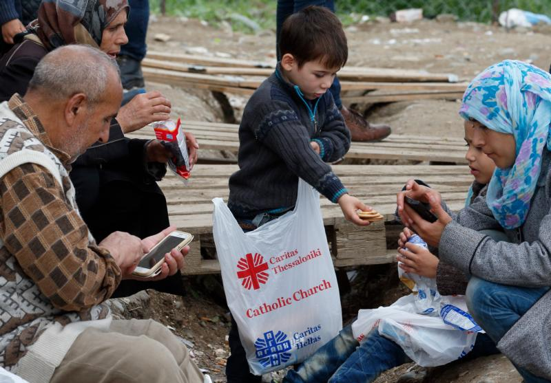 A boy hands cookies from a food bag given by Caritas to family members at a transit camp for refugees in Idomeni, Greece, on the border of Macedonia Oct. 19. Thousands of refugees are arriving into Greece from Syria, Afghanistan, Iraq and other countries and then traveling further into Europe. (CNS photo/Paul Haring)