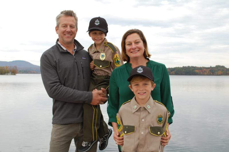 """Andrew, Bennett, Katherine (""""Kakki"""") and Chase Stenger pose on the shore of Lake Memphremagog in Newport, Vt., Oct. 13 after the boys rode on a state police boat as part of a Make A Wish adventure. Bennett is undergoing treatment for cancer. (CNS photo/Cori Fugere Urban, Vermont Catholic Magazine)"""