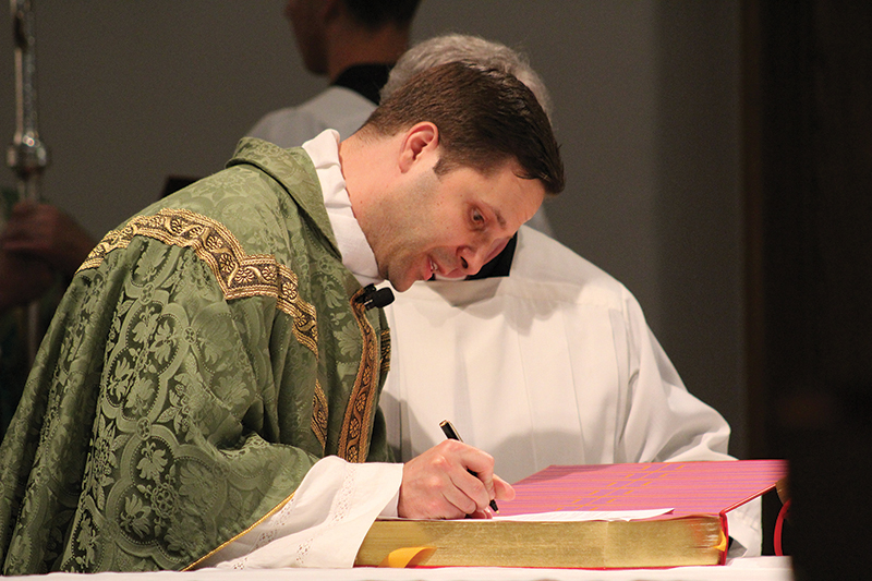 Father Brandon Farrar signs the oath of fidelity as he is installed as pastor of Sacred Heart Parish in Emporia.