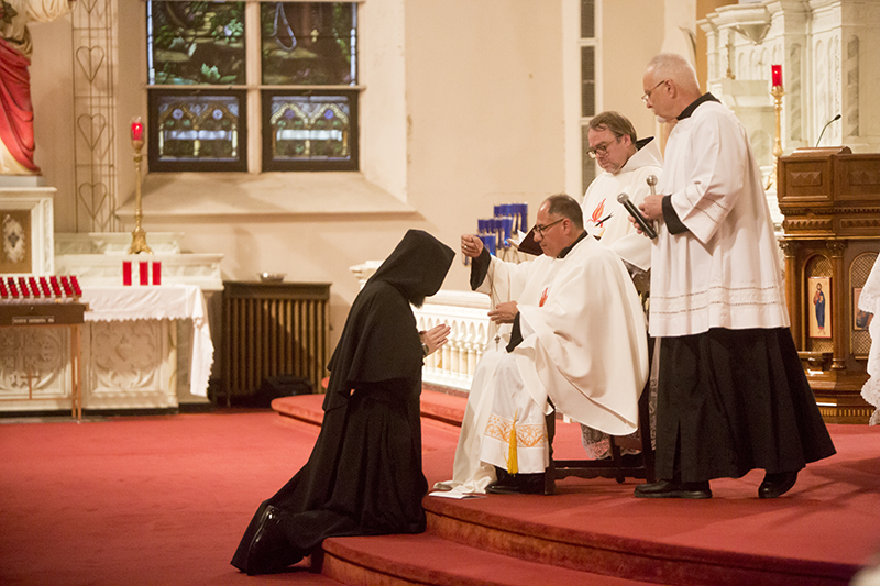 Leaven photo by Rachel Thompson Father Peter Jaramillo (seated), SSA, the prior of the Society of St. Augustine, presents Brother Elias Thelen with a the cross that completes the order's habit, as Brother Elias professes first vows to become a member of the society. He is assisted by Father Joseph Arsenault, SSA, and Michael Smith (right).