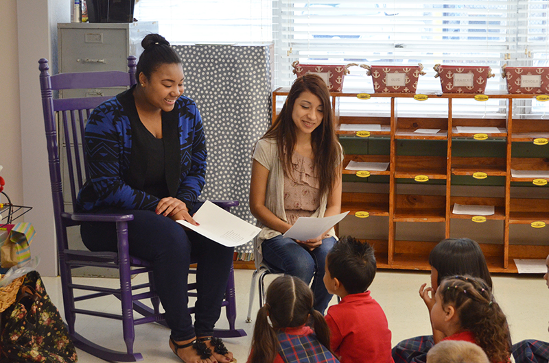 photos courtesy of Donnelly College Donnelly College students, from left, Ravi Allgood and Cynthia Reyes, read examples of their own poetry to students at Resurrection Catholic School at the Cathedral in Kansas City, Kansas.