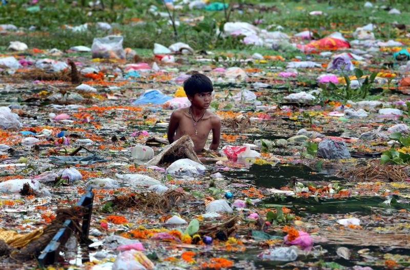 In this Sept. 9, 2014, file photo, a young man collects items on Jawahar Lal Nehru Lake after a festival in Bhopal, India. Some doctors say patients have a right to have causes of illness, especially from environmental pollution, studied as part of their care. (CNS photo/Sanheev Gupta, EPA)
